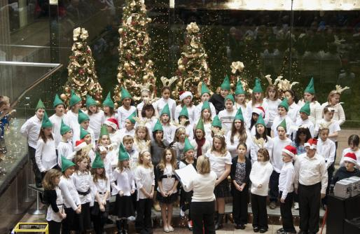 Holiday Choir in white shirts and green hats