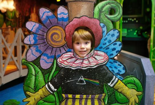 Child posing in munchkinland flower
